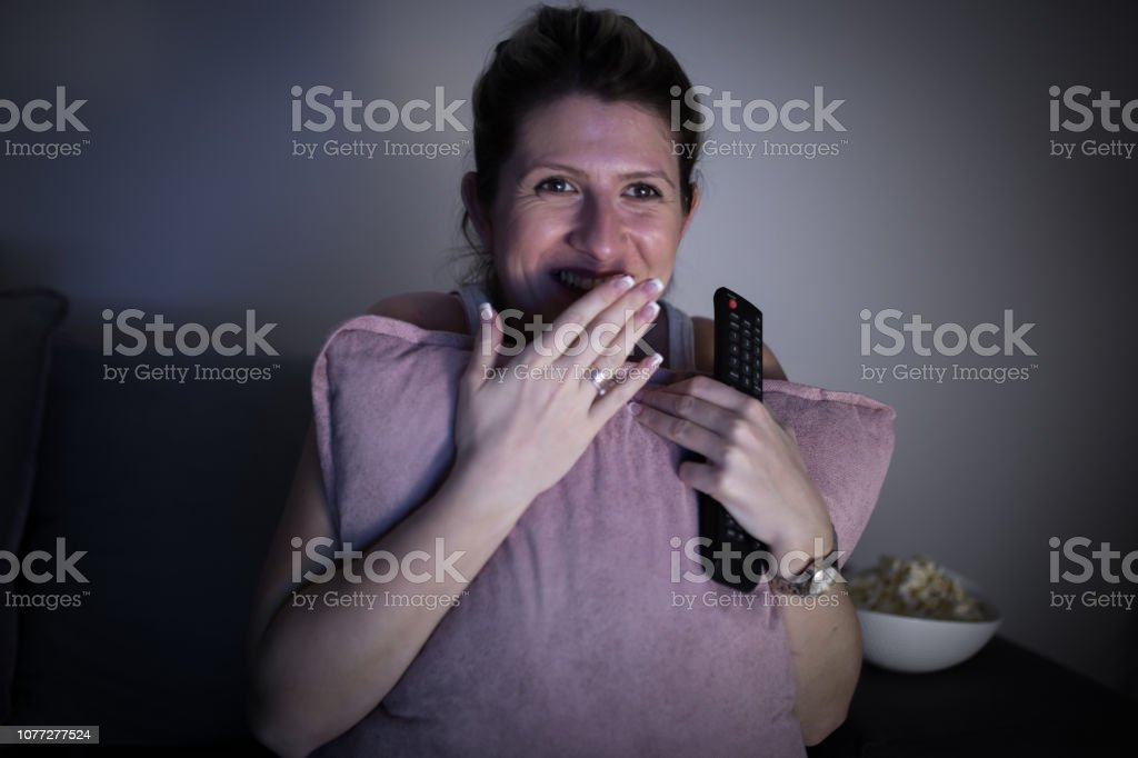 Young pregnant wife watching funny movie stock photo
