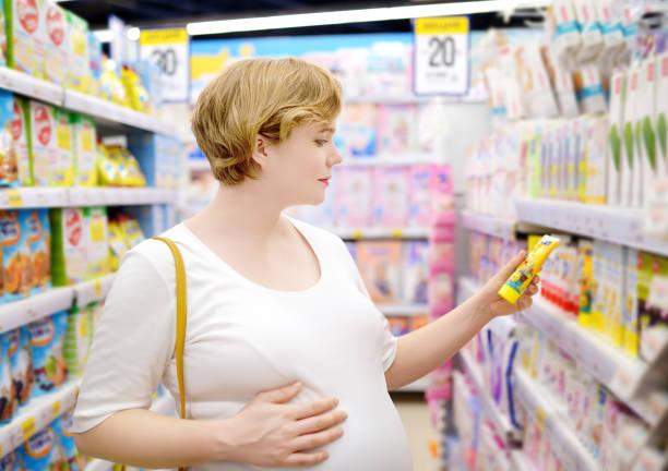 Mujer embarazada joven eligiendo cosméticos y productos de cuidado en la tienda para recién nacidos - foto de stock