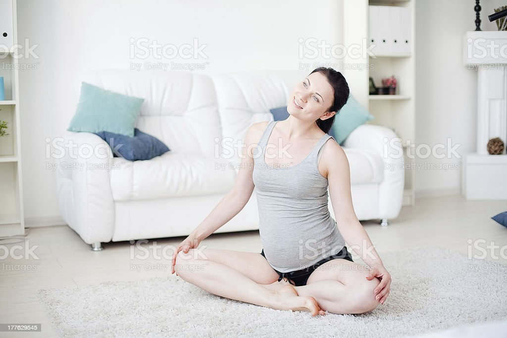 Young pregnant woman do yoga indoors royalty-free stock photo