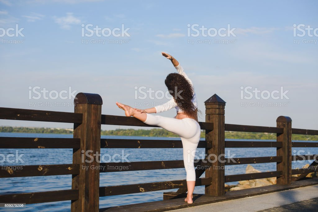 Young pregnant woman doing yoga by the river stock photo