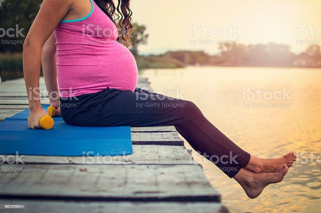 Young pregnant woman doing yoga exercises at the lake royalty-free stock photo