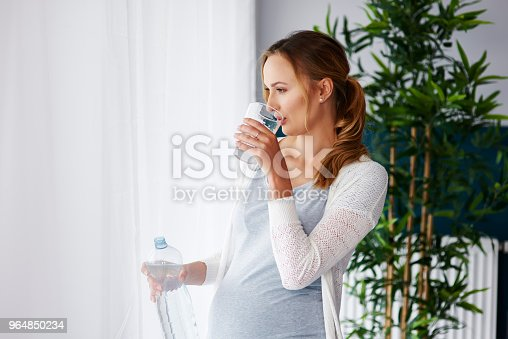 Young pregnant woman drinking water
