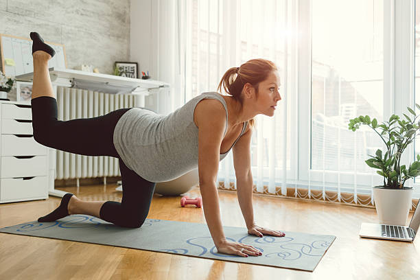 young pregnant woman exercise in her living room. - prenatal care stock pictures, royalty-free photos & images
