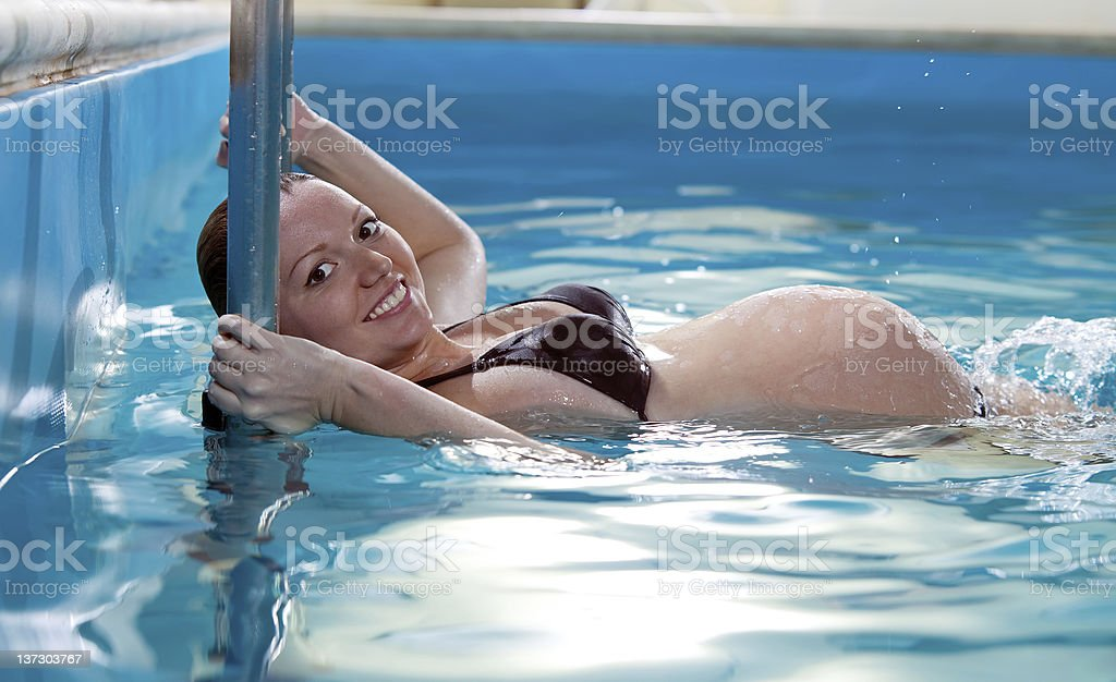 Young pregnant woman in swimming pool stock photo