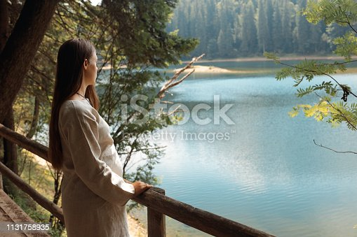 A pregnant woman rests after walking on a wooden bridge with a beautiful view of the lake. Healthy lifestyle concept