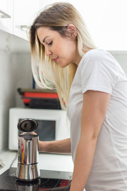 Young pregnant woman is pouring coffee in the kitchen stock photo