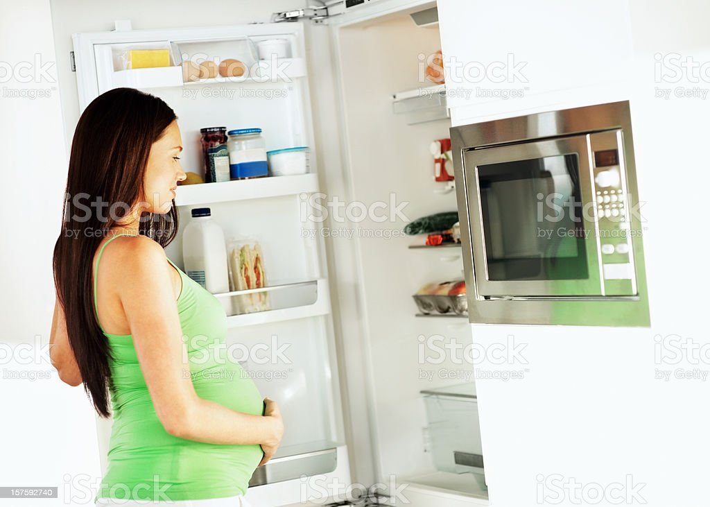 Young pregnant woman looking into the refrigerator royalty-free stock photo