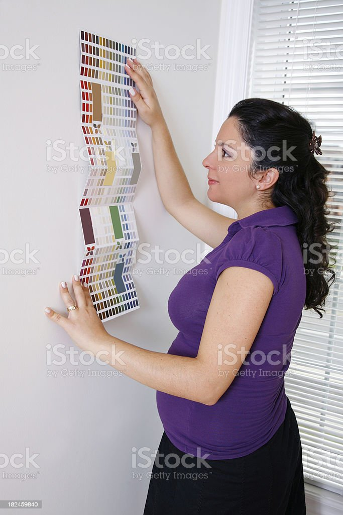Mujer embarazada joven mirando sobre colores para la nueva Nursery foto de stock libre de derechos