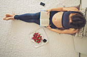 Young pregnant woman, lying in bed with smartphone, book, coffee and fruits, motherhood concept