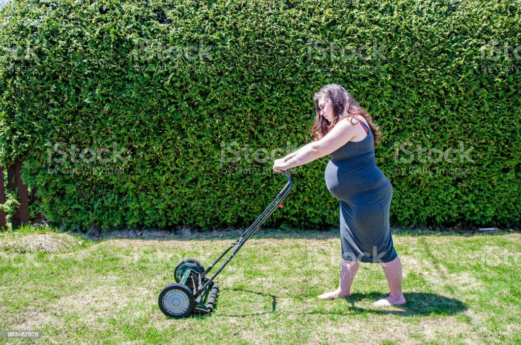 Young pregnant woman mowing the lawn with manual lawn mower in backyard stock photo