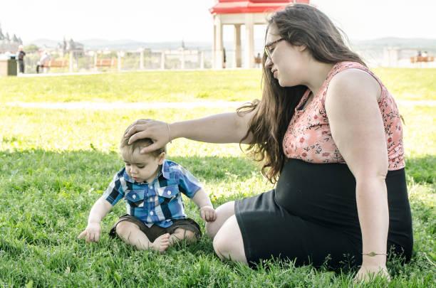 Junge schwangere Frau spielt mit Baby Junge im Park – Foto