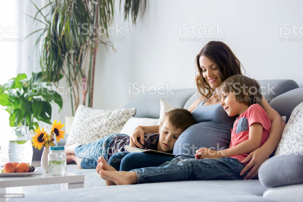 Young pregnant woman, reading book at home to her boys stock photo