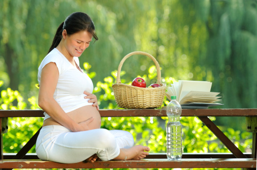 1071305850 istock photo Young pregnant woman relaxing at a park 182855798
