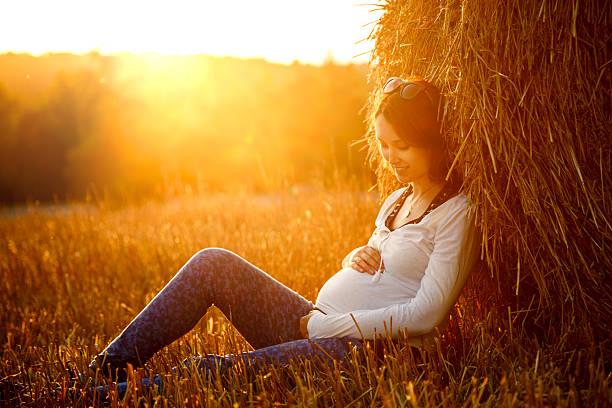 Junge schwangere Frau Sitzen im Heuhaufen – Foto