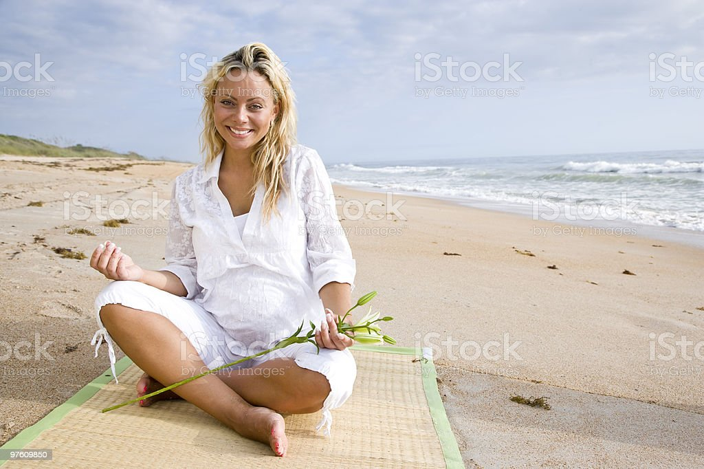 Young pregnant woman sitting on beach royalty-free stock photo