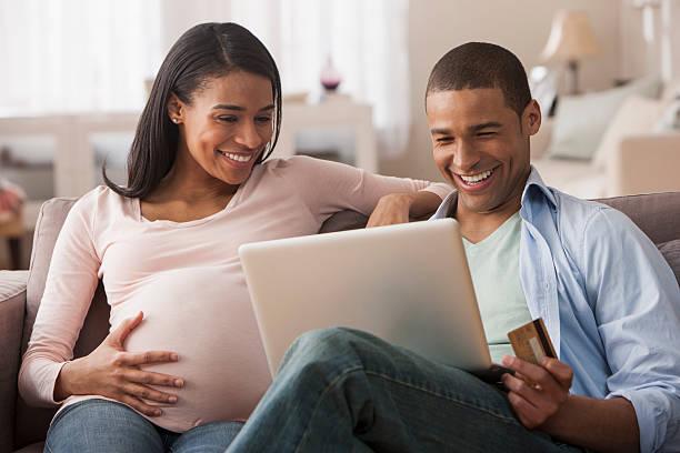 junge schwangere frau sitzen mit ehemann macht online-einkauf - schwanger werden rechner stock-fotos und bilder