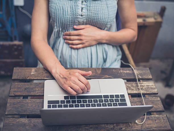 young pregnant woman with laptop outside - schwanger werden rechner stock-fotos und bilder