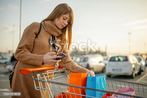 Young pregnant happy woman pushing shopping cart with groceries on sidewalk near supermarket and looks checking buying list on her mobile phone. She is beautiful and attractive