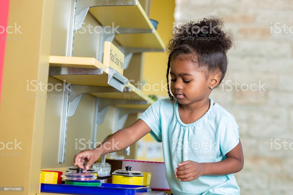 Young preschool girl playing with a toy kitchen stock photo