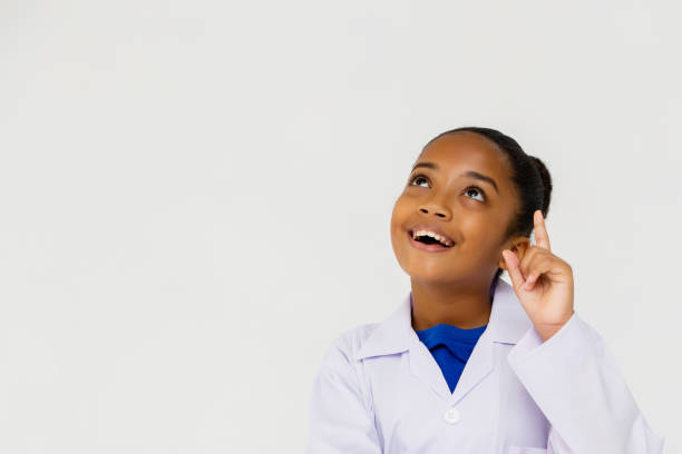 Young preteen African American kid wearing lab coat thinking stock photo