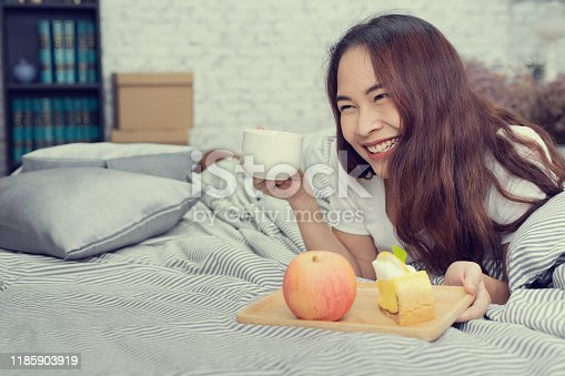 Beautiful happy yong woman eating breakfast with fruit and cake on bed, process filter vintage
