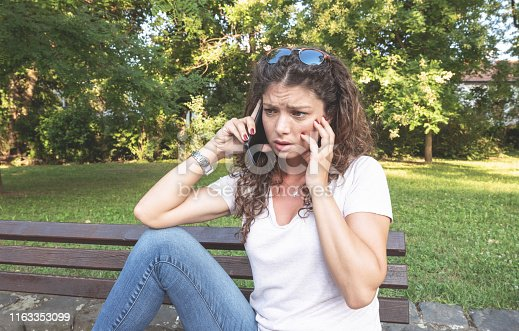 istock Young pretty attractive girl or woman sitting on the bench in the park talking and arguing with her boyfriend or husband on mobile phone with emotional sad depressed face expression while they talk 1163353099