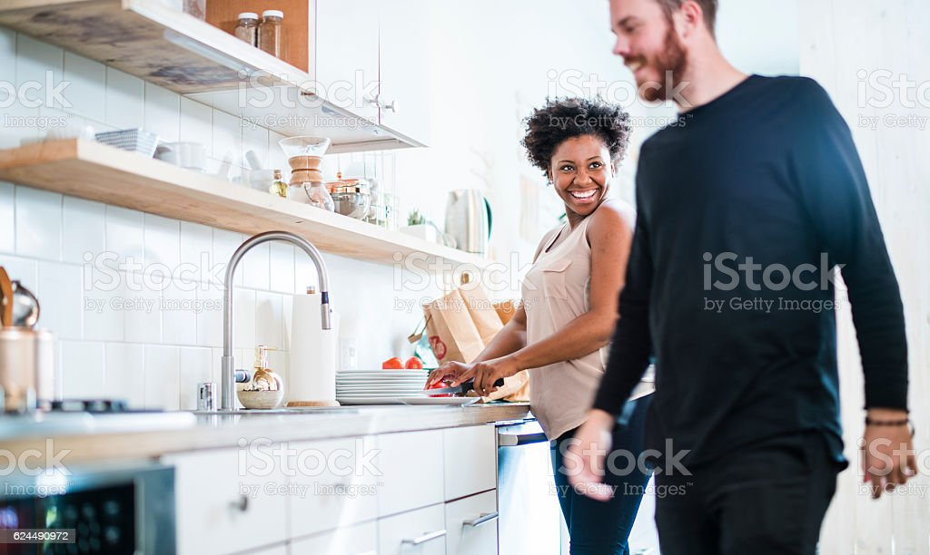 Young pretty black woman make soup in kitchen stock photo