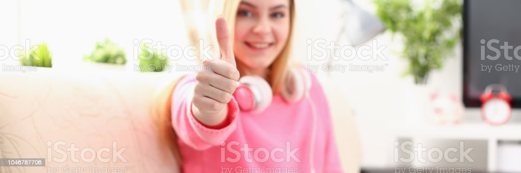 young pretty blond woman hold tablet in arms show big finger super...