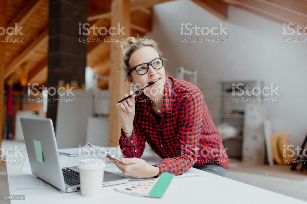 jung, hübsch, blonde Frau plant auf dem Notebook und tablet-die Erweiterung von ihrem loft – Foto