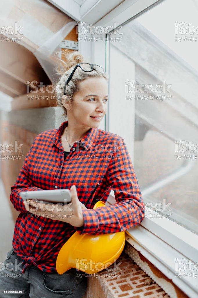 jung, hübsch, blonde Frau mit gelben Helm plant auf dem Notebook und tablet-die Erweiterung von ihrem loft – Foto