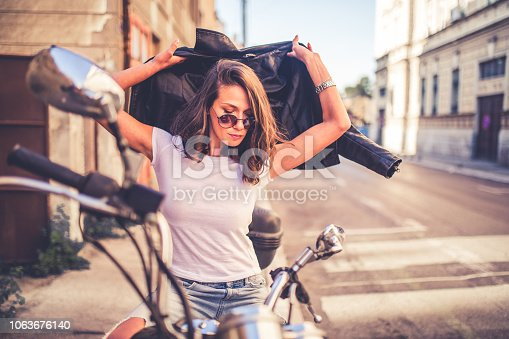 Young pretty fashioned girl sitting on her motorcycle