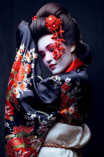 junge schöne geisha in kimono mit sakura und dekoration - kimono stock-fotos und bilder