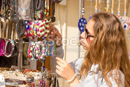 istock Young pretty girl chooses traditional jewelery at the Turkish bazaar in the old city in Antalya - Antalya, Turkey, 04.23.2019 1145644578