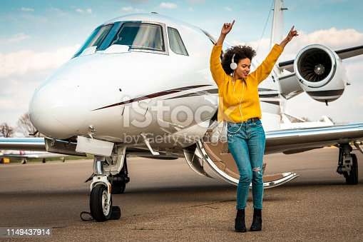 Young pretty girl dancing to the beats of her favorite tracks with her hands up while listening to music over the headphones next to a private airplane parked on an airport runway.