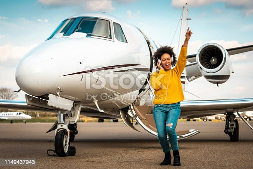 Young pretty girl dancing to the beats of her favorite tracks while listening to music over the headphones next to a private jet parked on an airport tarmac.
