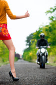 beautiful young attractive girl hitchhiker motobiker on the road in a forest area