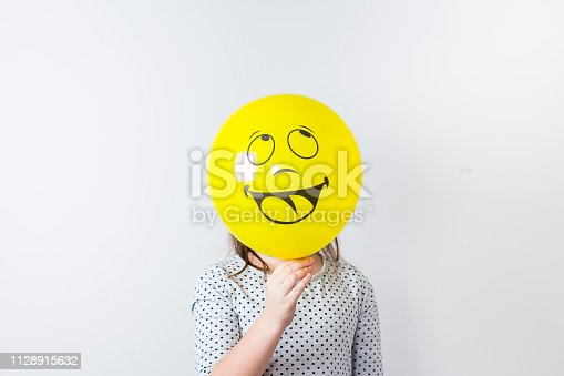 istock Young pretty girl holding baloon over white background. April fools Day. Smile baloon 1128915632