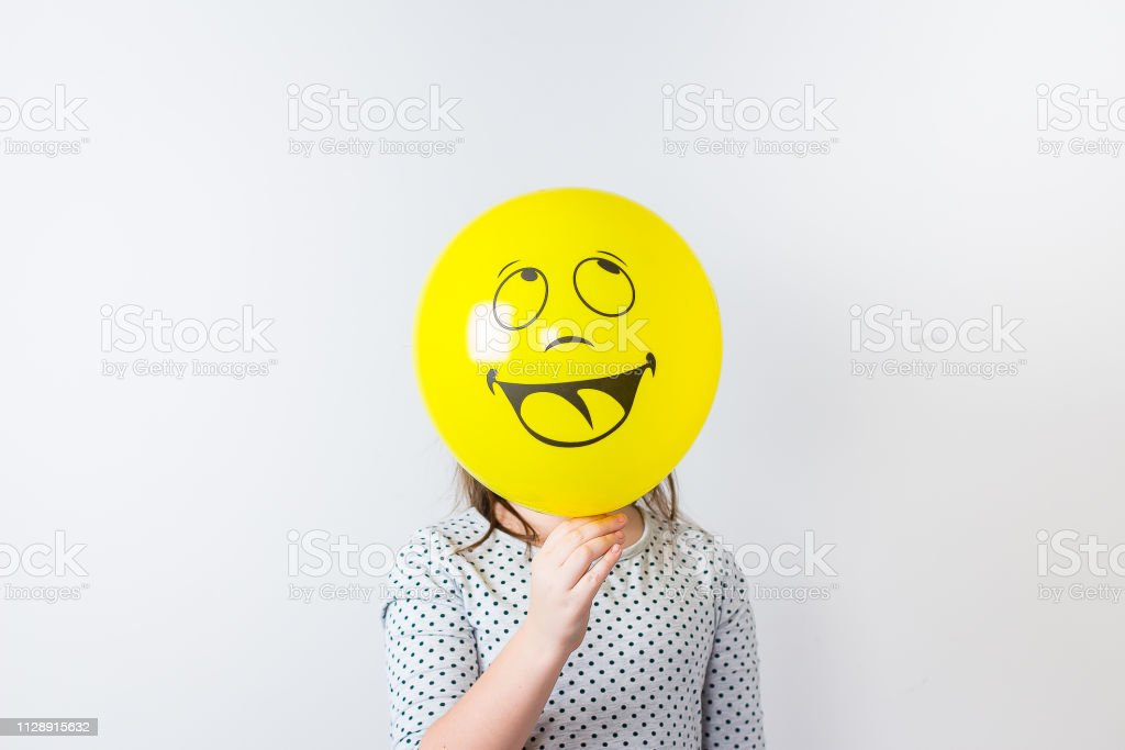 Young pretty girl holding baloon over white background. April fools Day. Smile baloon stock photo
