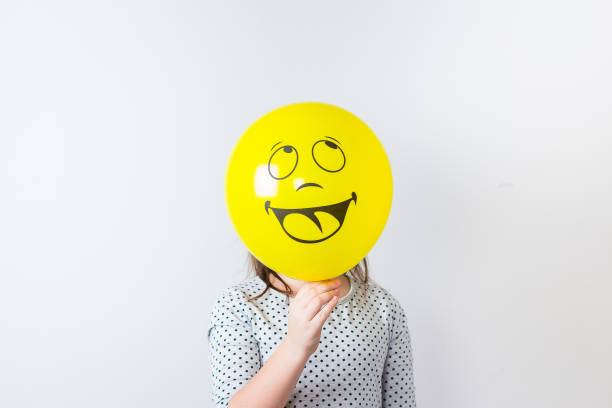 young pretty girl holding baloon over white background. april fools day. smile baloon - april fools stock photos and pictures