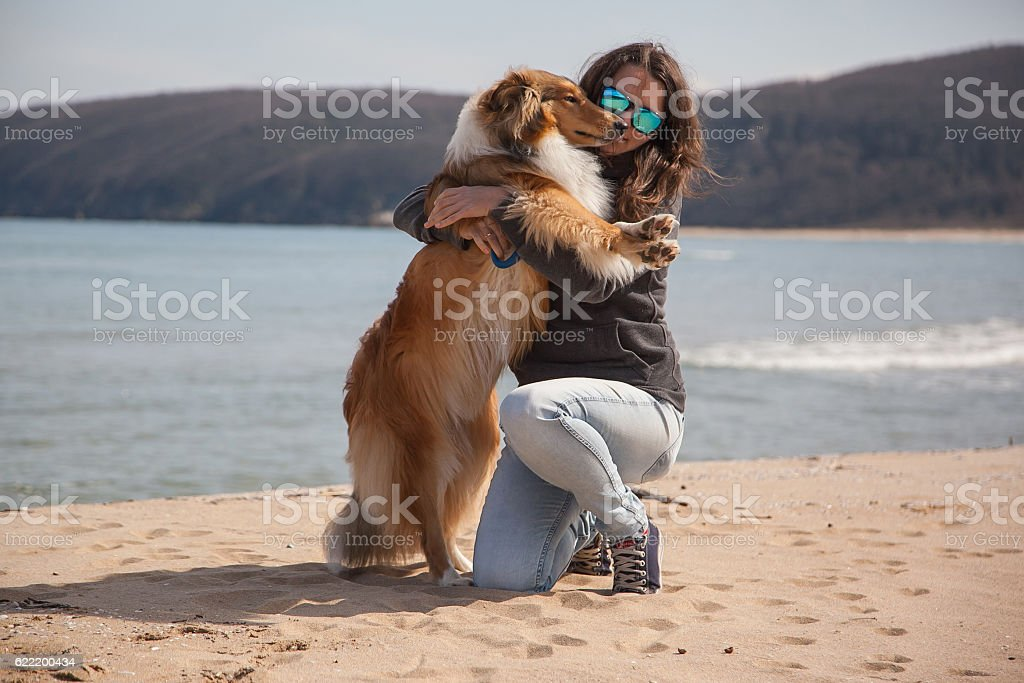 Young pretty girl hugging rough collie dog at the beach stock photo