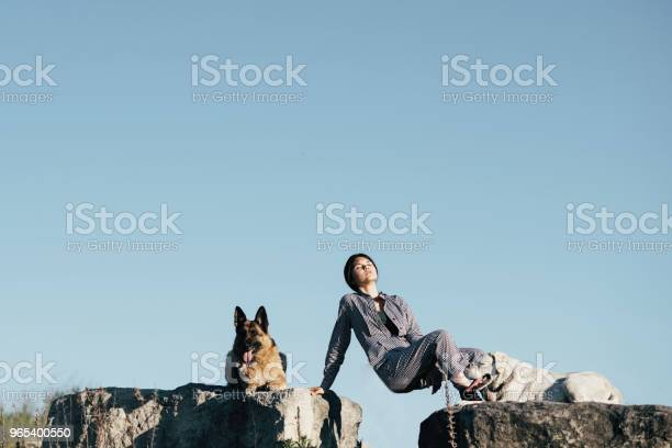 Foto de Jovens E Belas Garota Posando Para O Fotógrafo Deitado Sobre Uma Grande Pedra Ao Lado Os Cães e mais fotos de stock de Adulto