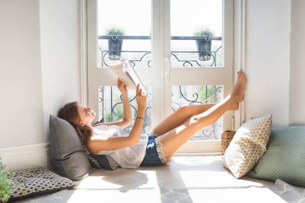 joven linda a chica leyendo la revista de moda junto a la ventana - gente tranquila fotografías e imágenes de stock