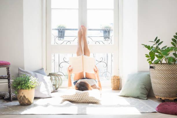 mooi meisje lezing mode-tijdschrift in de buurt van venster - woman home magazine stockfoto's en -beelden