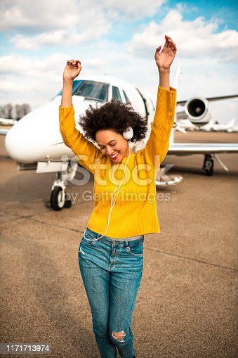 Young pretty girl rocking to her favorite music she's listening to over her headphones on an airport runway next to a private airplane.