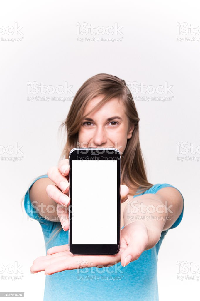 Young Pretty Girl Shows Her phone White Background stock photo