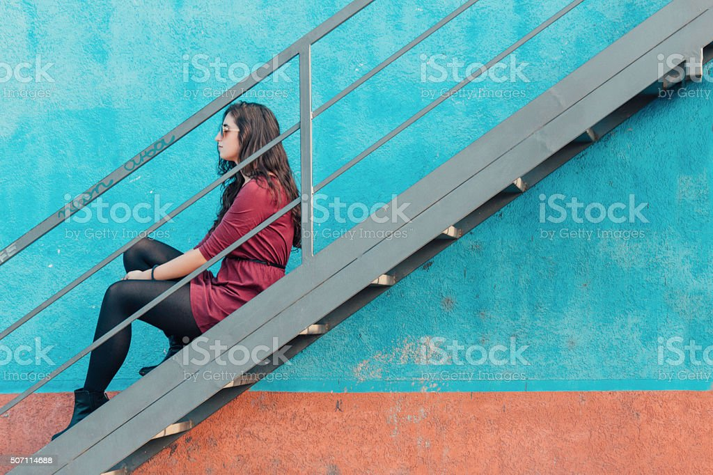 Young pretty girl sitting on the staircases and resting stock photo