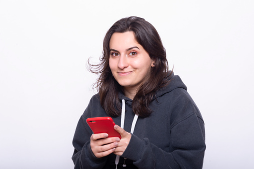Young pretty girl standing in front of white background, looking towards camera with phone in hand.
