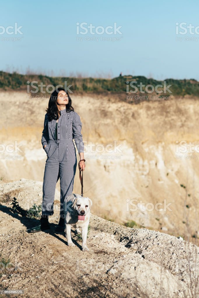 Jeune fille jolie, promener un chien contre une fosse de sable - Photo de Amitié libre de droits