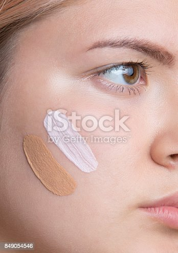 istock Young pretty girl with two color foundations on face. 849054546