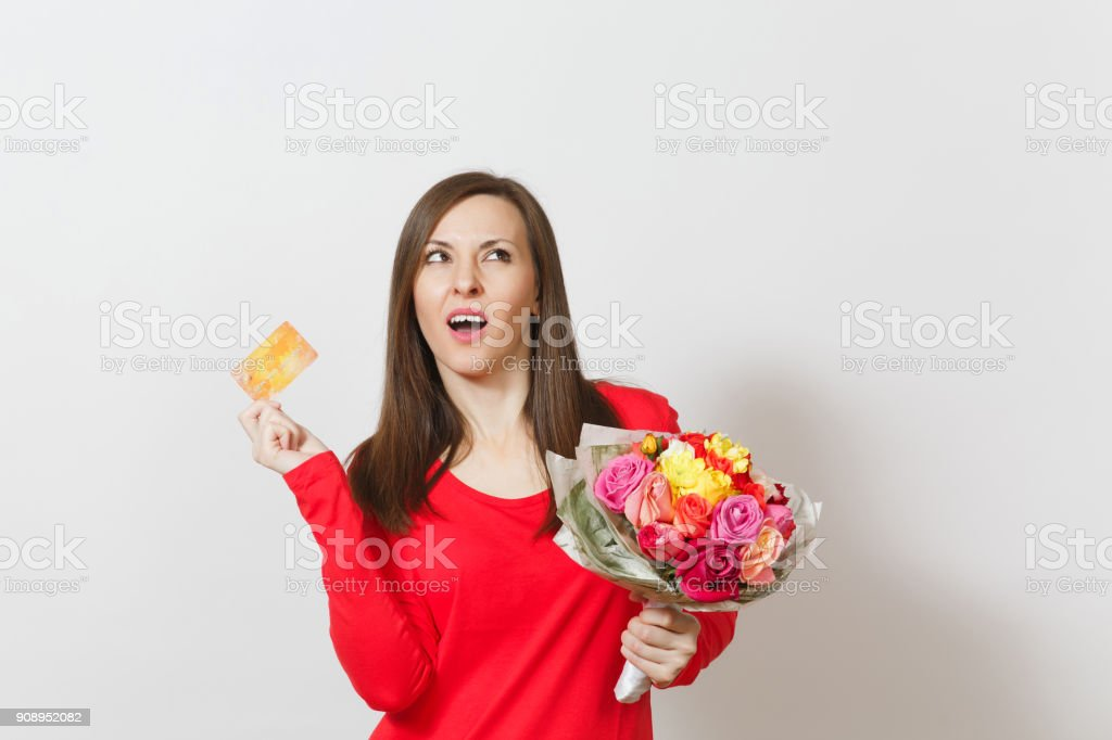 Young pretty indignant woman holding bouquet of beautiful roses flowers credit card isolated on white background. Copy space for advertisement. St. Valentine's Day or International Women's Day concept stock photo